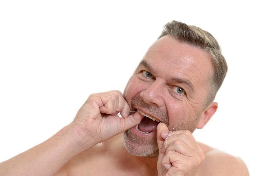 Man Flossing His Teeth With Dental Floss